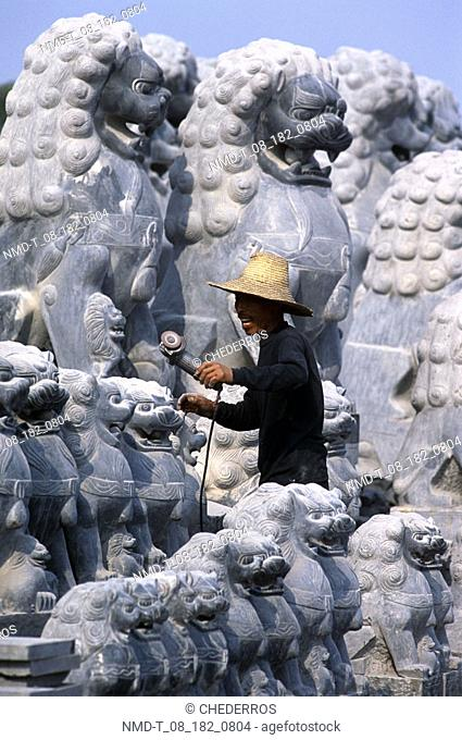 Side profile of a man standing in front of statues, China
