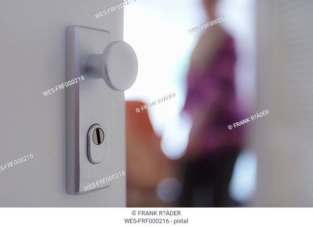 View through open apartment door to senior woman