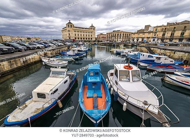 Local fisherman's boats at the marina in Syracuse city, southeast corner of the island of Sicily, Italy. Old Post Office on background