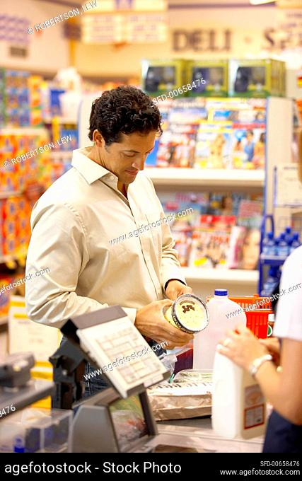 Man examining groceries at supermarket check-out