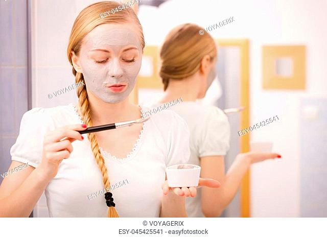 Skincare. Blonde woman in bathroom applying with brush gray clay mud mask to her face. Young lady taking care of skin. Spa beauty wellness