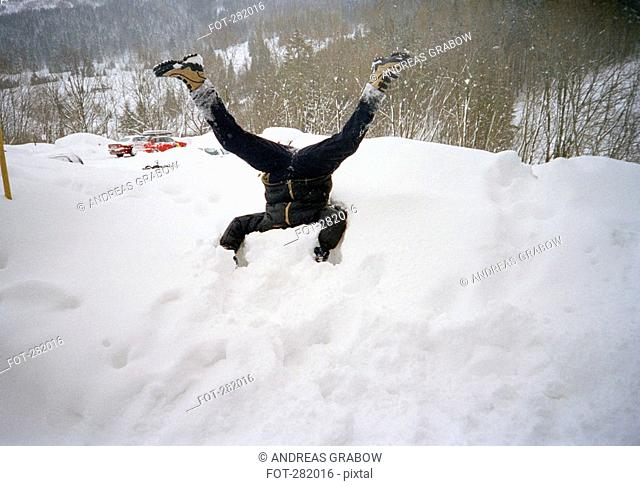 Man with head buried in pile of snow