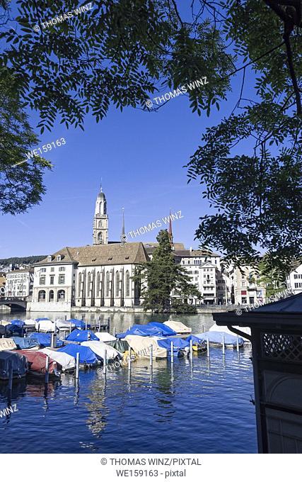 Boats moored at River Limmat, Grossmünster Church in the distance, Zurich , Switzerland