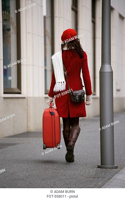 A woman walking along the street with a suitcase
