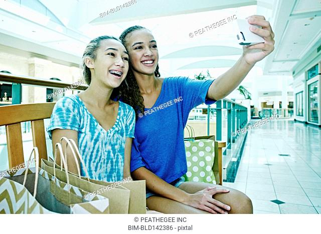 Mixed race teenage girls taking cell phone photograph at shopping mall