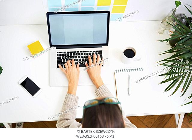 Young woman working at desk with laptop