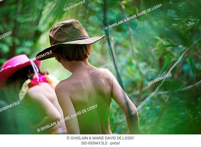 Rear view of girl and boy wearing cowboy hats playing in garden bushes