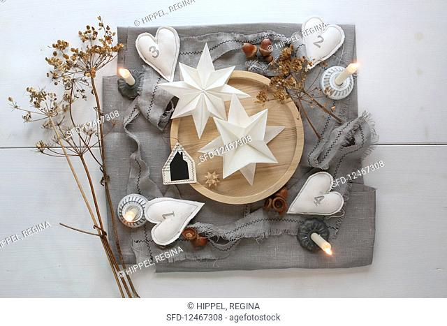 An original Advent calendar with decorative paper stars on a wooden tray and homemade fabric hearts with numbers