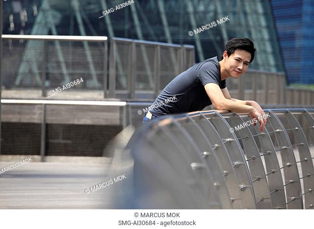 Young man leaning on railing smiling