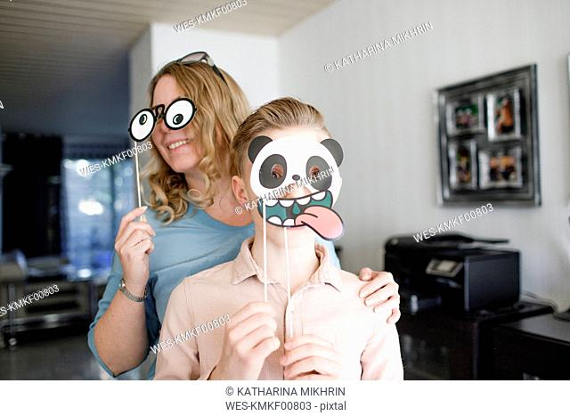 Mother and son playing with carnival masks