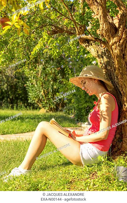 Woman sitting under a tree in garden reads a book