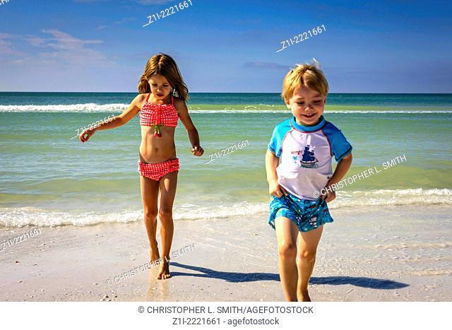 Two young children playing at Siesta Key beach Sarasota Florida