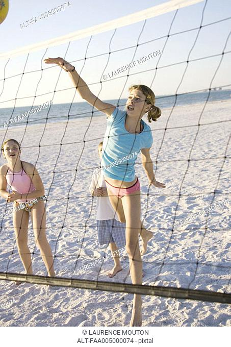 Preteen girls playing beach volleyball