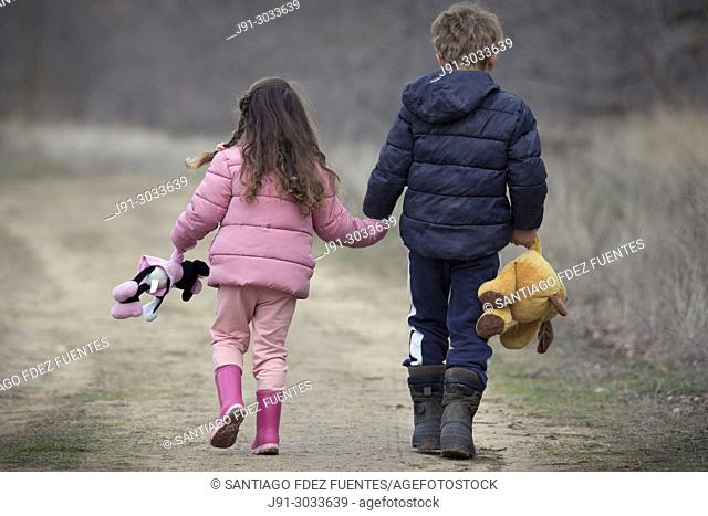 Two kids with their stuffed animals lost in countryside. Spain