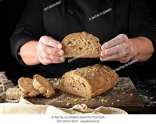 chef in black uniform keeps cut off a piece of bread baked from rye flour and pumpkin seeds, black background