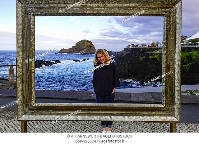 Porto Moniz, Madeira, Portugal A woman framed by a picture frame, at the natural pools attached to the ocean for swimming and bathing
