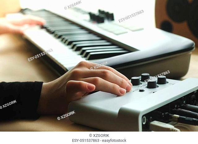 A woman in a black jacket adjusts the synthesizer on the music console, while the other hand plays the synthesizer