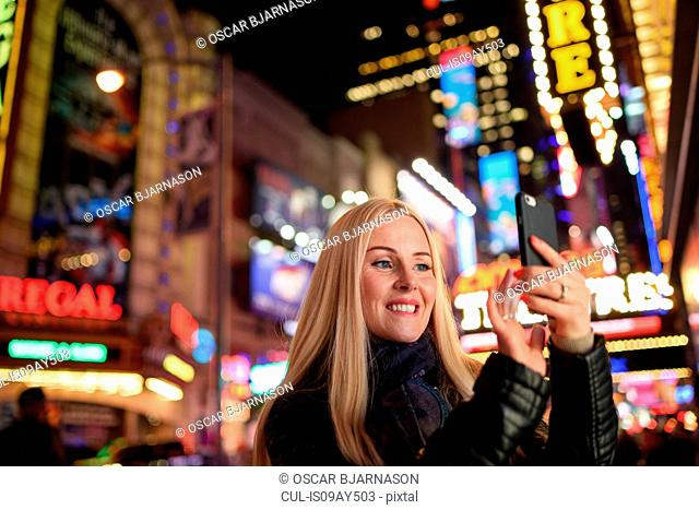 Female tourist taking smartphone selfie with neon signs in Times Square at night, New York, USA