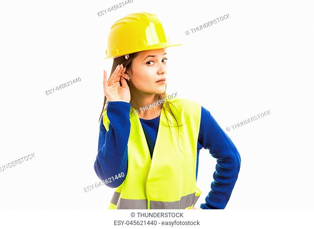 Young attractive female engineer making hear gesture by touching her ear as paying attention to gossip concept isolated on white background