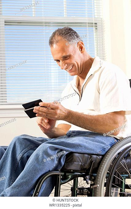 Man with spinal cord injury in wheelchair using a smart phone
