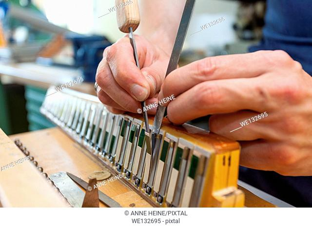 Instrument maker fixing reeds of accordion, tuning, focus on hands