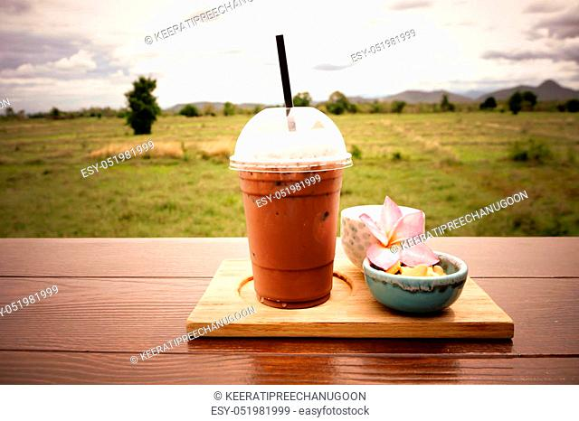 iced coffee and biscuit alphabet with rice field background