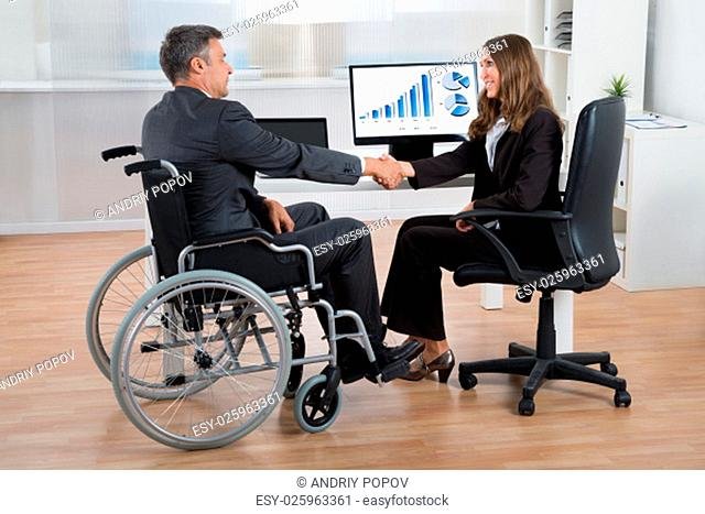 Happy Businesswoman Shaking Hands With Disabled Businessman In Office