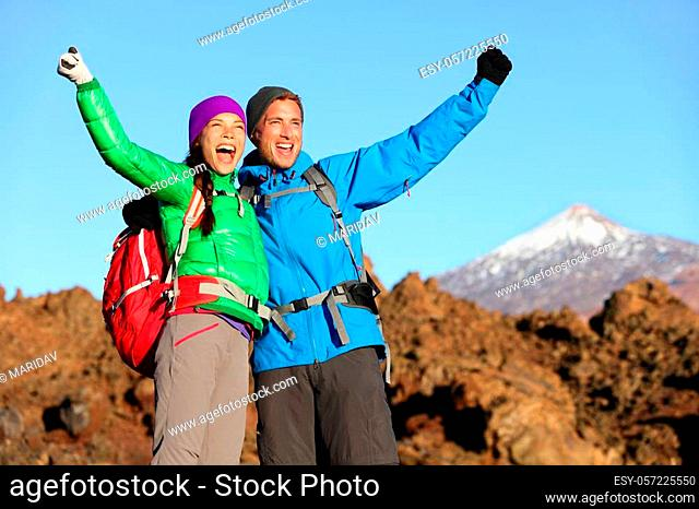 Happy celebrating winning hiking people at top. Cheering hiker couple enjoying freedom on hike with arms raised in mountain landscape