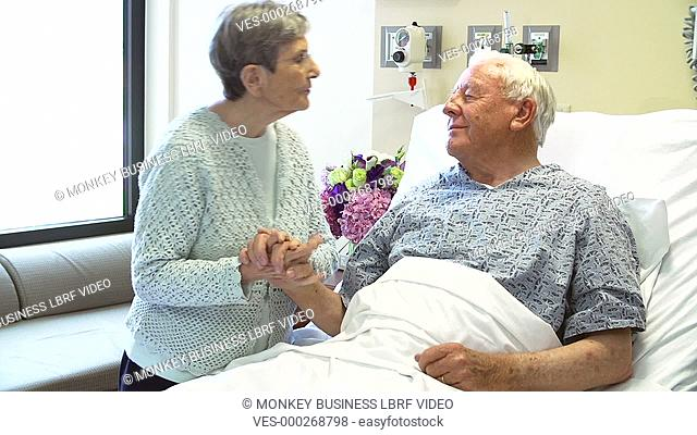 Senior man is pleased to see wife as she visits him in hospital.Shot on Sony FS700 in PAL format at a frame rate of 25fps