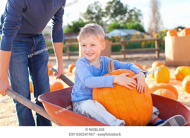 cheerful little boy sitting in the cart with huge pumpkin, having fun with his father at pumpkin patch