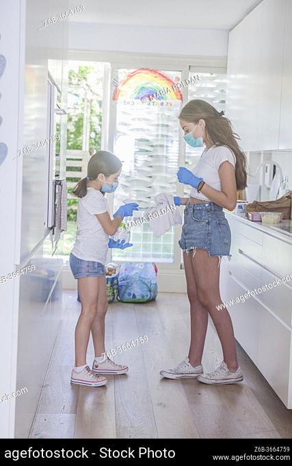 2 sisters with masks and gloves cleaning in the kitchen