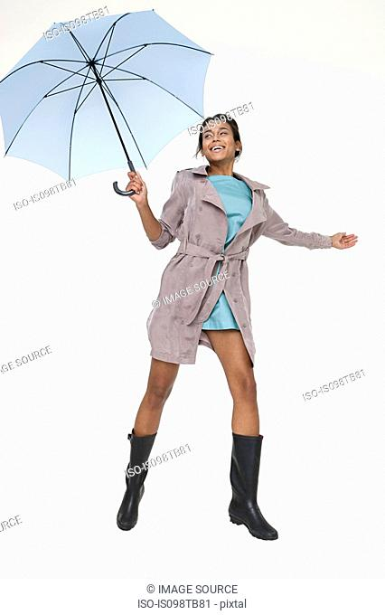 Young woman holding umbrella and jumping