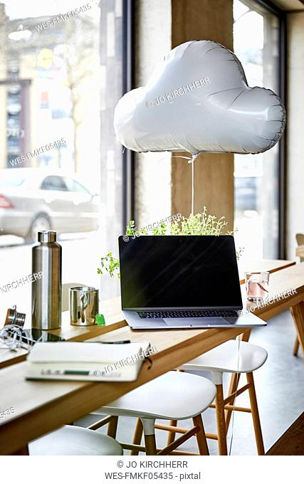 Creative office with cloud balloon and laptop