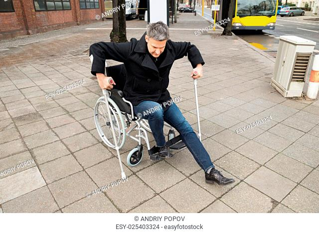 Disabled Man Trying To Walk With The Help Crutches