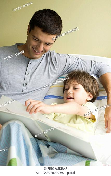 Father and son reading book together in bed