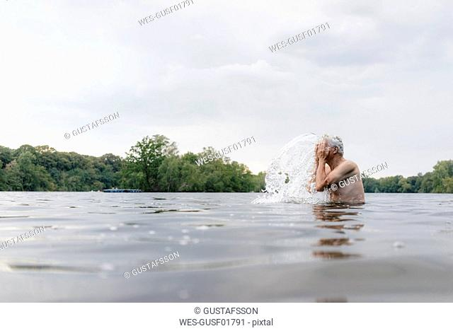 Senior man in a lake splashing water in his face