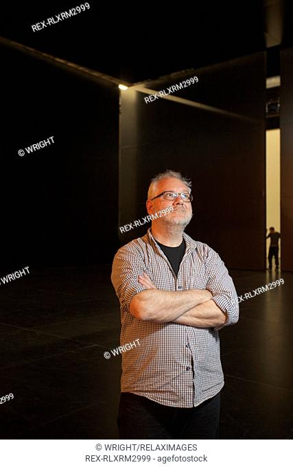 Mature man standing arms crossed in backstage of opera house
