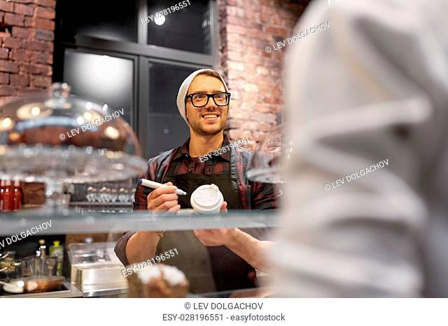 small business, people and service concept - happy man or barman with coffee cup and marker serving female customer at vegan cafe