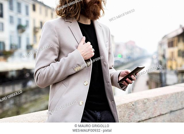 Stylish young man outdoors holding cell phone