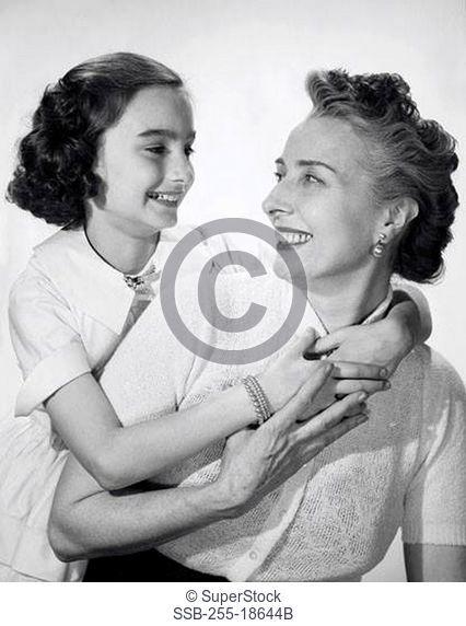 Studio shot of girl hugging her grandmother and smiling