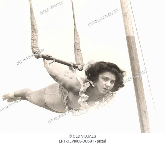 Female trapeze artist in mid-air