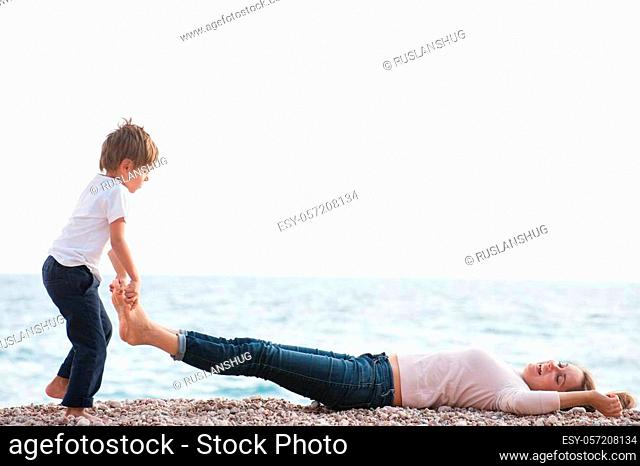 funny kid lifting happy mother legs playing on ocean shore in autumn season