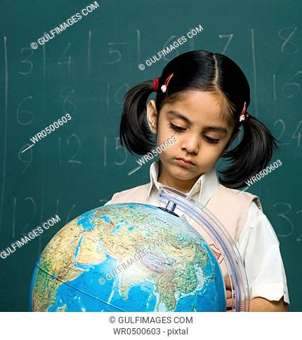 Girl 6-7 in classroom looking at globe