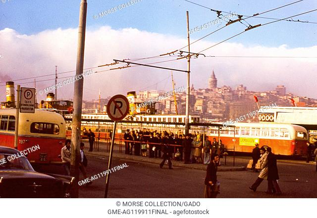 View of a busy outdoor bus station and ferry landing at the shoreline of the Bosphorus, in Istanbul, Turkey, November, 1973