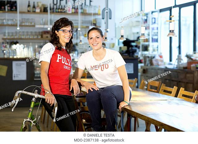 Two young women posing at the coffee bar. One of them sitting on a race bicycle and the other on a table. Milan (Italy), July 2014