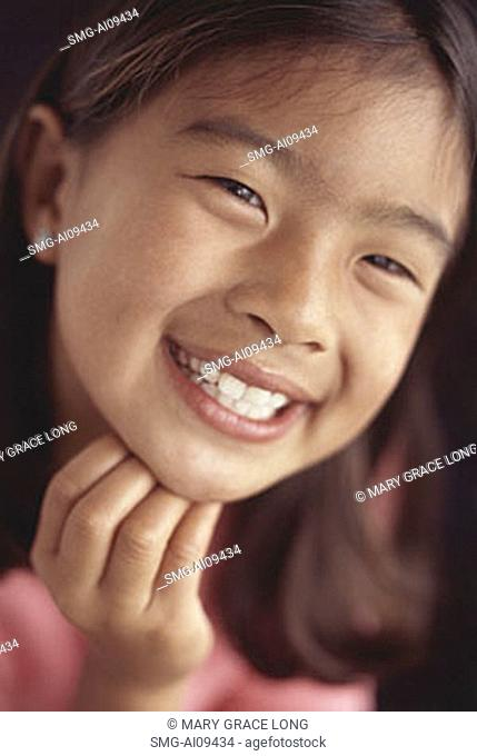 Young girl smiling with hand on chin