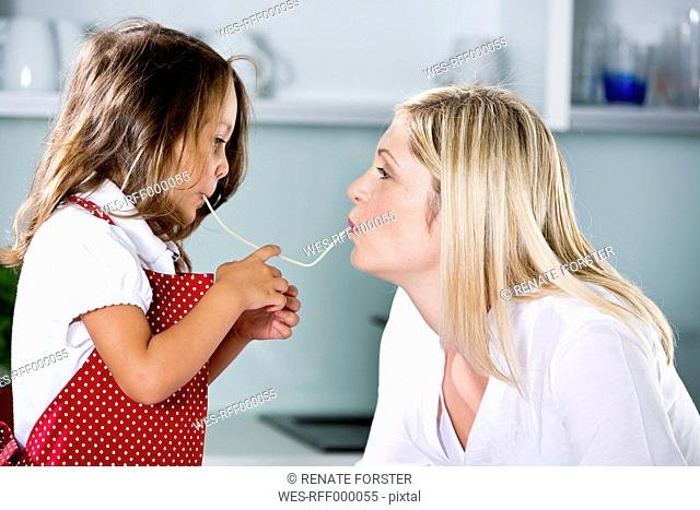 Germany, Daughter eating noodles with mother in kitchen