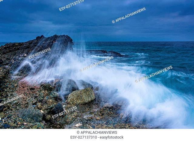 Wave crashing on a rock at Table Rock Beach, in Laguna Beach, California