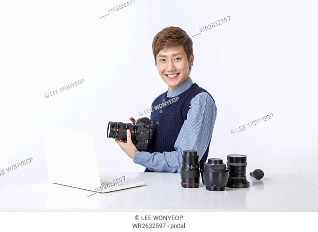 Portrait of young smiling man collecting cameras