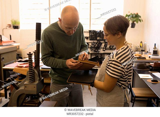 Male and female worker checking leather sheet